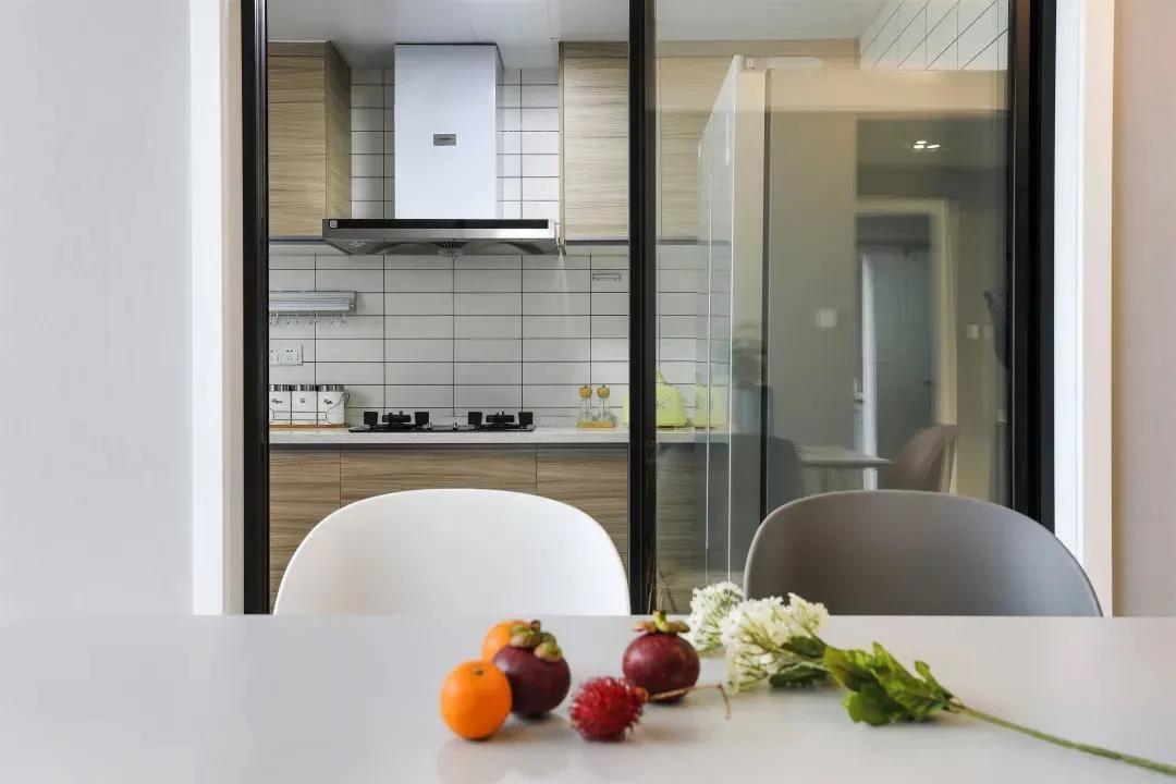厨房是比较清新雅致的原木橱柜搭配白色方砖,起到了视觉延伸的效果,也使整个厨房干净整洁。
