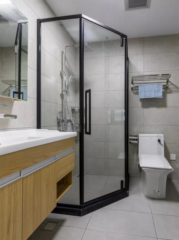 卫生间设计了干湿分离,淋浴房用玻璃门与洗漱台马桶隔断。灰色的地砖搭配黑框淋浴门,整体风格简单。