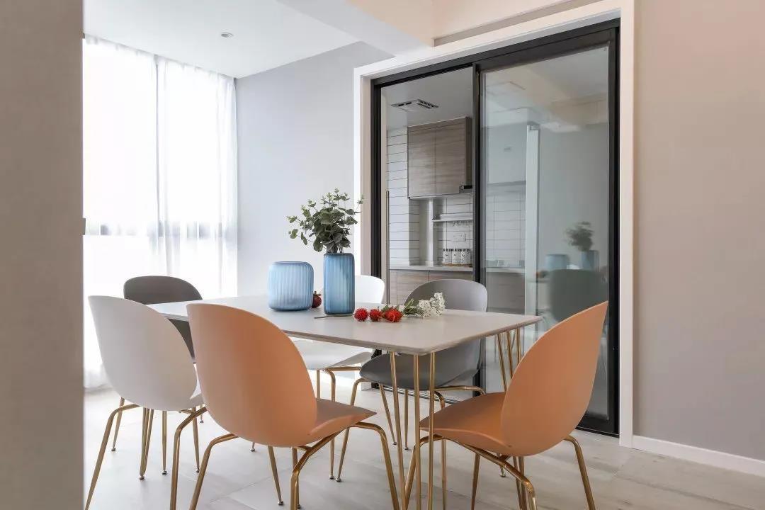 餐厅与客厅在同一空间,位置靠近落地窗,旁边玻璃推拉门内是厨房区域,整个餐厨区的采光通透性都好到没话说。