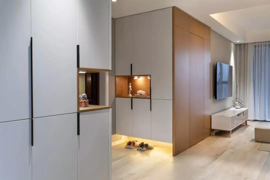 玄关柜设计的非常简洁大方,中部和底部留空的位置都装了暖色系灯带照明,仿佛在和你说欢迎回家。